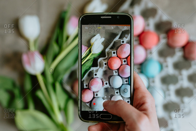 Hands taking a photo of Easter eggs with phone