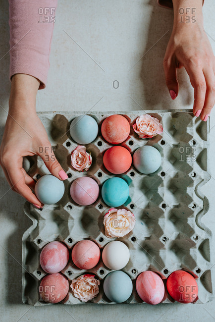 Person holding pastel Easter egg next to the other Easter eggs in carton