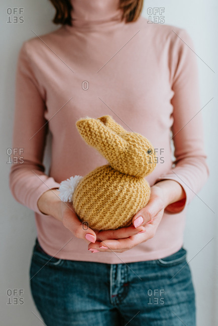 Person wearing pink shirt holding cute knitted Easter bunny