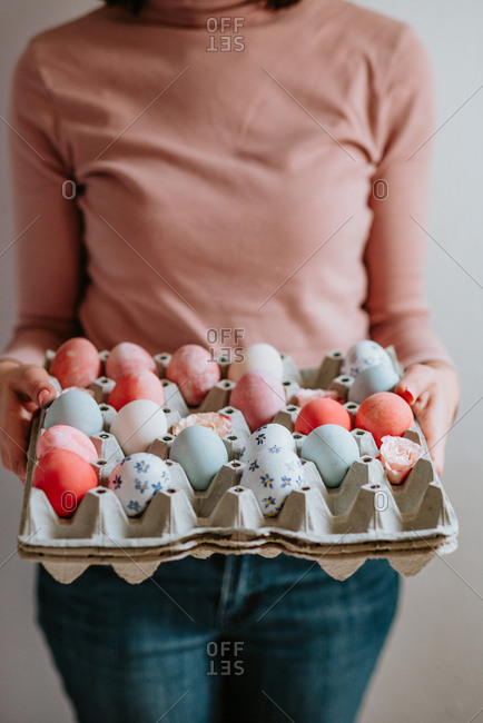 Woman wearing pastel colors holding carton of pastel Easter eggs
