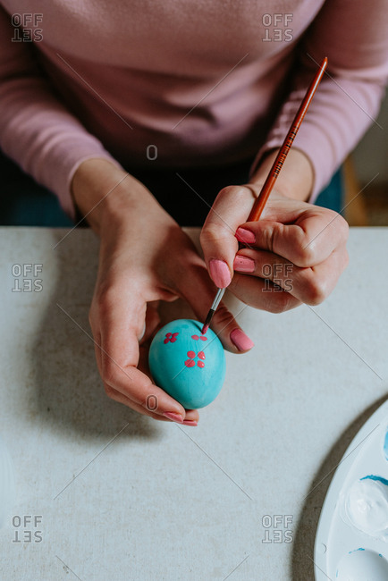 Hands coloring turquoise Easter egg with pink paint