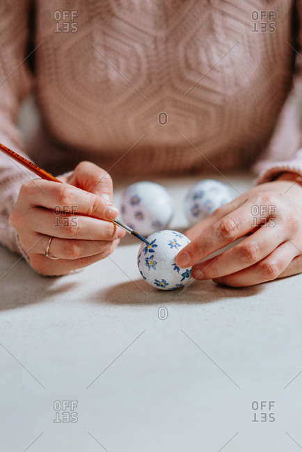 Hands painting Easter eggs on the table