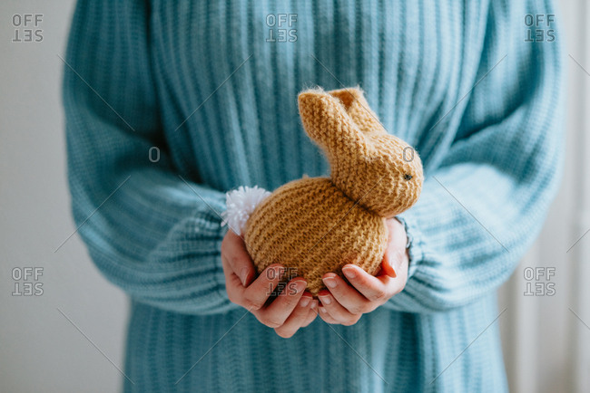 Person in pastel blue sweater holding cute knitted Easter bunny