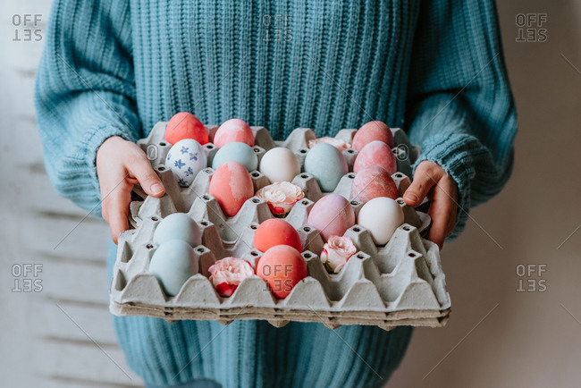 Person in pastel blue sweater holding carton of pastel pink and blue Easter eggs