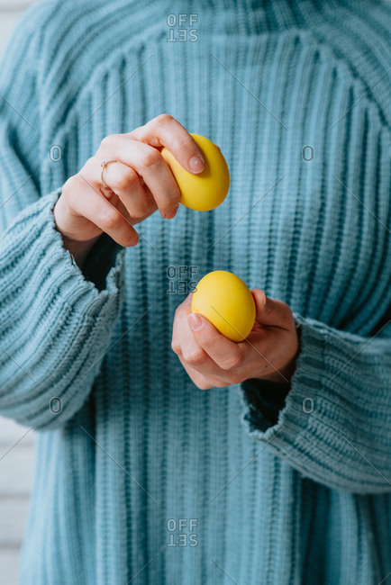 Person in pastel blue sweater holding three yellow Easter eggs