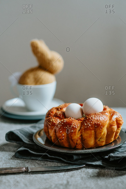 Easter braided nest like pastry with eggs inside and knitted bunny in the background