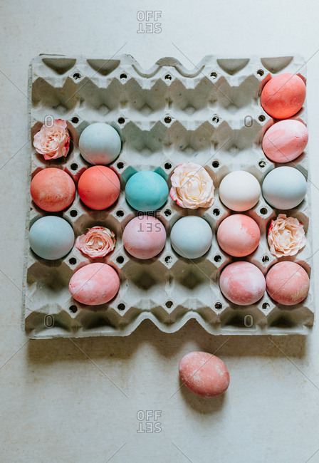 Flatlay shot of pastel pink and turquoise Easter eggs in carton