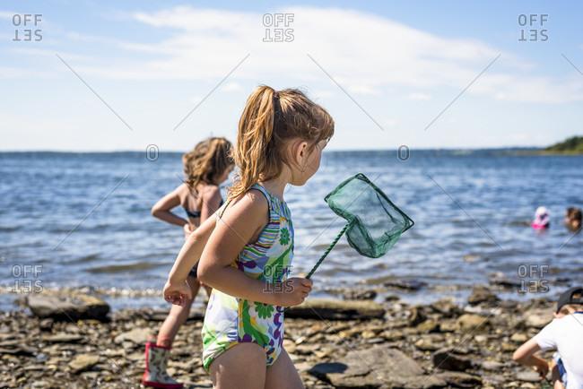 Girl on coastline with fishing net, Bristol, Rhode Island, USA