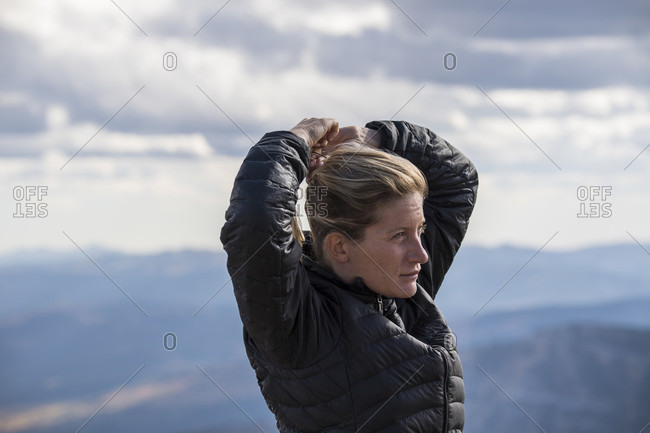 Woman preparing for outdoor adventure by securing ponytail against mountain background, Jackson Hole, Wyoming, USA