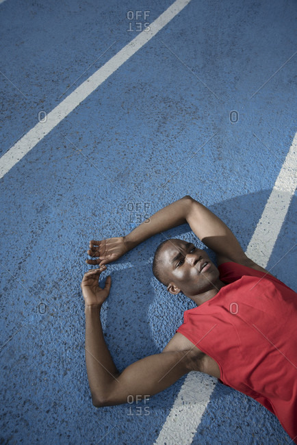 Runner lying while resting on sports track, Barcelona, Catalonia, Spain
