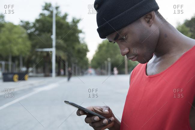 Sportsman in street using mobile phone, Barcelona, Catalonia, Spain