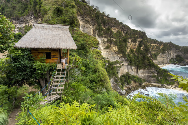 Woman sitting outside thatched roof hut on coast with cliffs, Nusa Penida, Bali, Indonesia