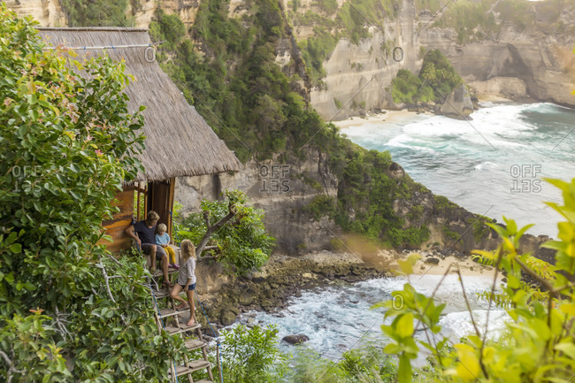 Family on vacations outside thatched roof hut on coastline, Nusa Penida, Bali, Indonesia