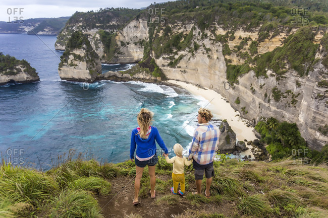 Family on vacations looking at view of coastline with cliffs, Nusa Penida, Bali, Indonesia