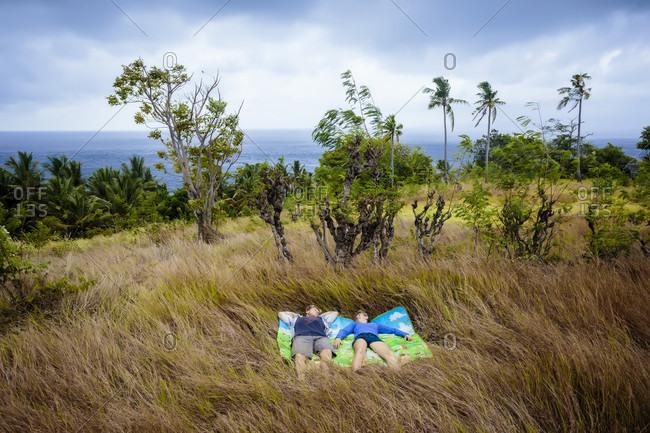 Couple lying on blanket in meadow near ocean coastline, Nusa Penida, Bali, Indonesia