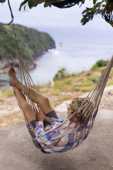Man relaxing in hammock, Nusa Penida, Bali, Indonesia