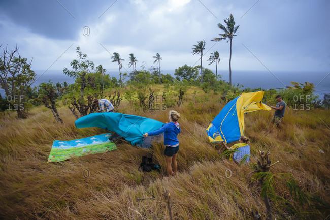 People setting up tent in meadow, Nusa Penida, Bali, Indonesia