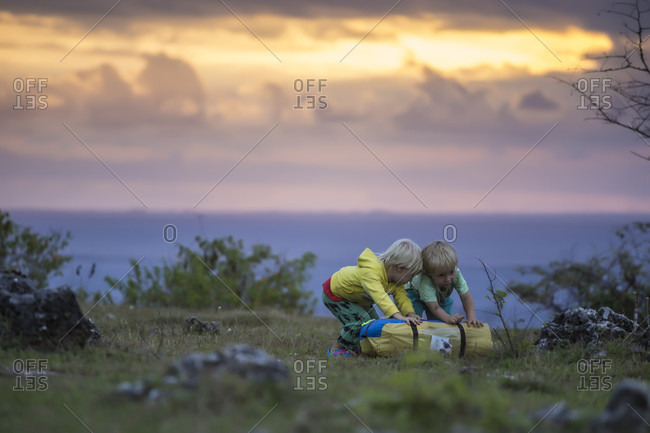Two boys playing with tent bag at sunset, Nusa Penida, Bali, Indonesia