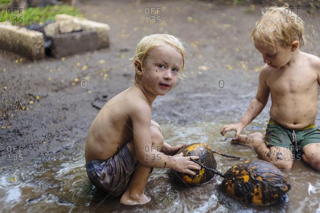 Two boys playing in mud, Nusa Penida, Bali, Indonesia