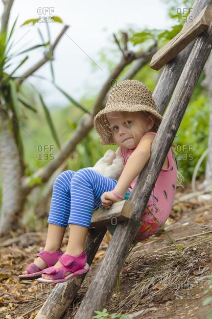 Girl sitting on ladder and looking at camera, Nusa Penida, Bali, Indonesia