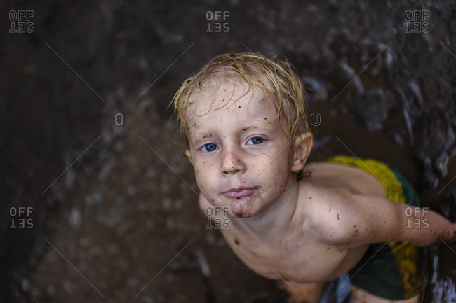 Boy playing in mud, Nusa Penida, Bali, Indonesia