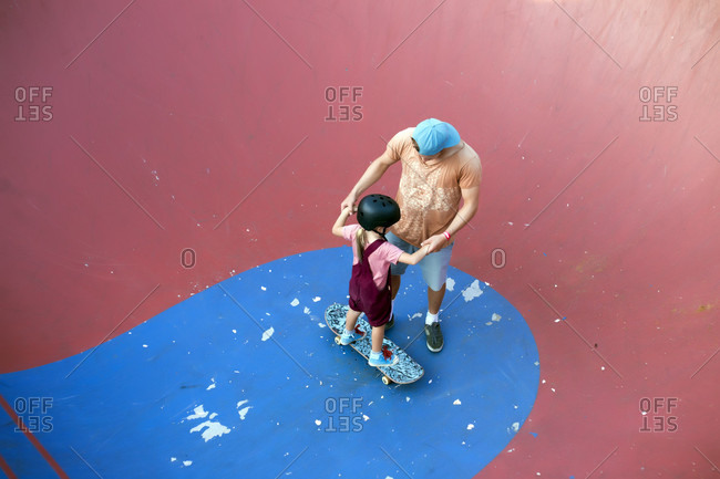 Father supporting daughter on skateboard in skate park, Canggu, Bali, Indonesia
