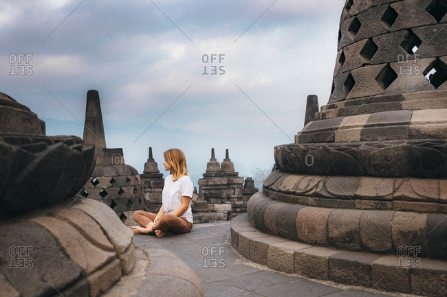 Woman sitting among stupas at Borobudur temple, Magelang, Central Java, Indonesia