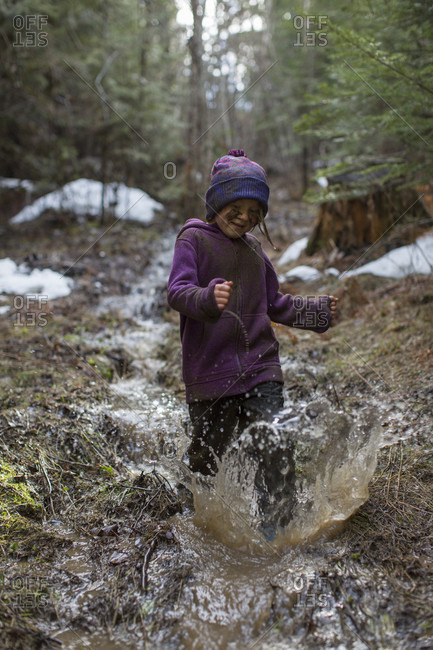 Girl splashing in stream in forest, Sandpoint, Idaho, USA