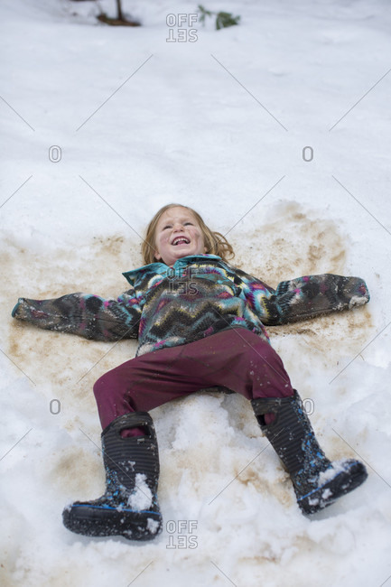Dirty girl making snow angel, Sandpoint, Idaho, USA