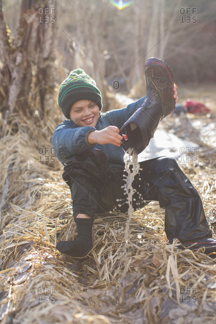 Boy pouring water out of rubber boot, Sandpoint, Idaho, USA