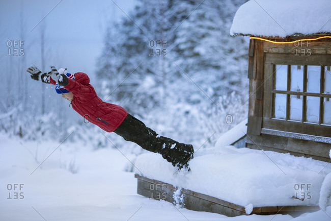 Young boy wearing winter clothes diving off porch into snow, Sandpoint, Idaho, USA
