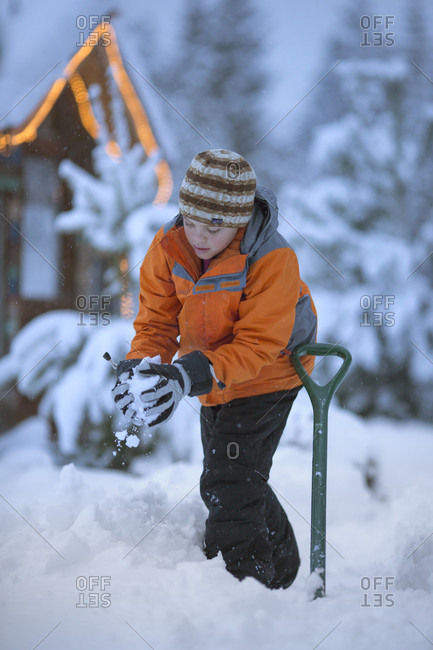 Young boy wearing winter clothes standing in snow and making snowball, Sandpoint, Idaho, USA