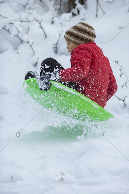 Young boy sliding on plastic sled, Sandpoint, Idaho, USA