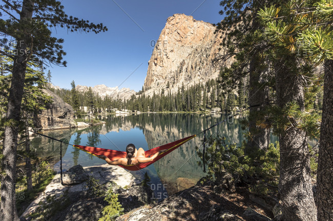 Female hiker relaxing in hammock between two pine trees overlooking Elephants Perch and Saddleback Lake, Sawtooth National Recreation Area, Stanley, Idaho, USA