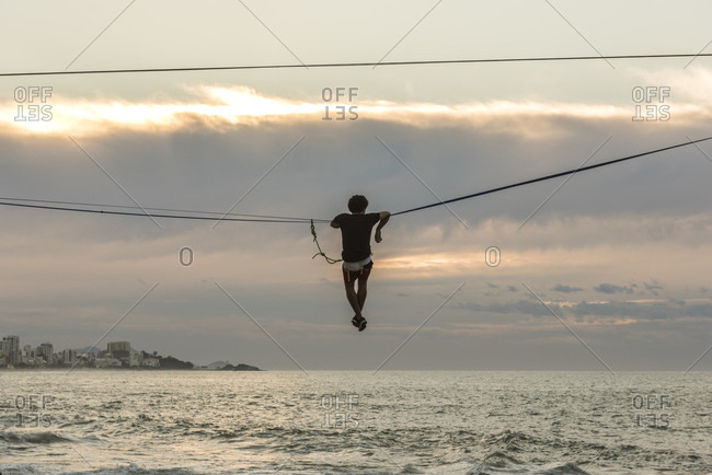 Man slack lining and water lining during sunrise in Leblon Beach, Rio de Janeiro, Brazil