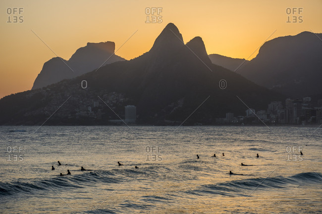 Surfers on water during sunset in Arpoador Beach, next to Ipanema in Rio de Janeiro, Brazil