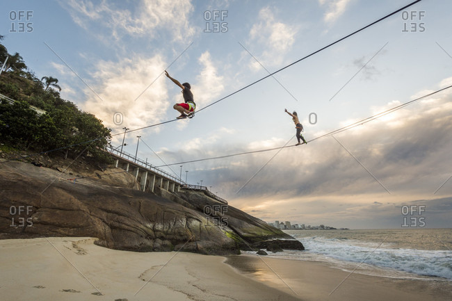 Man and woman slack lining and water lining during sunrise in Leblon Beach, Rio de Janeiro, Brazil
