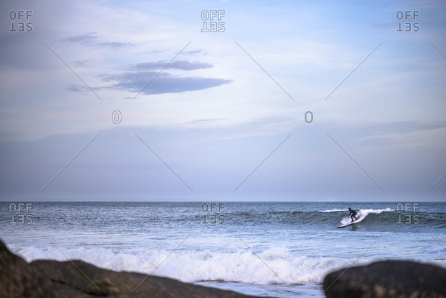 Surfer at dusk during winter swell in Rhode Island, Narragansett, Rhode Island, USA