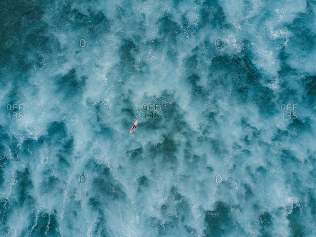 Aerial view of woman paddling on longboard surfboard in sea, Tenerife, Canary Islands, Spain