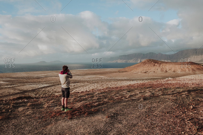 Photographer taking picture in volcanic landscape, Lanzarote, Canary Islands, Spain