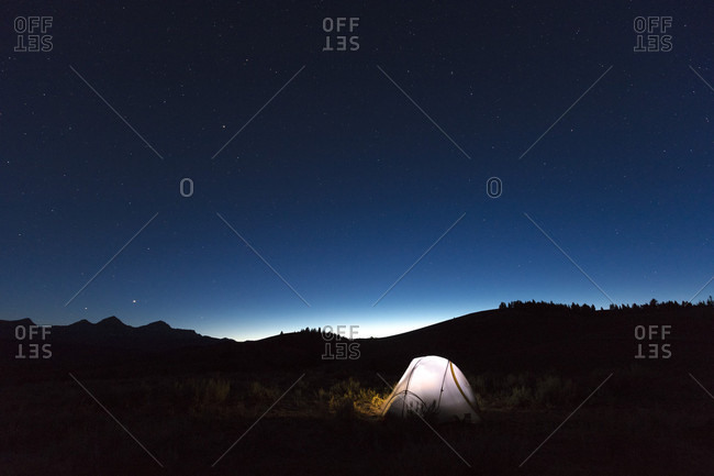 Illuminated tent under starry sky at night, Sawtooth Wilderness foothills, Stanley, Idaho, USA