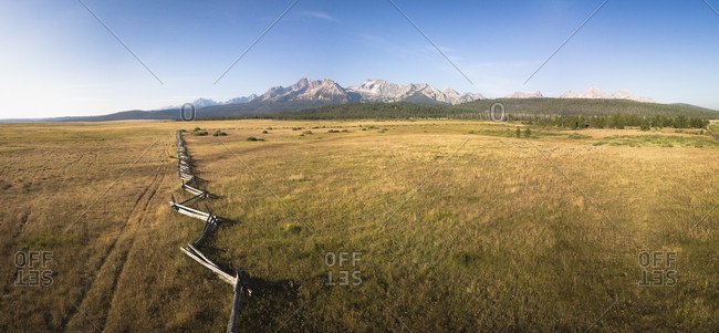 Wooden fence in meadow with Sawtooth Mountains in background, Stanley, Idaho, USA