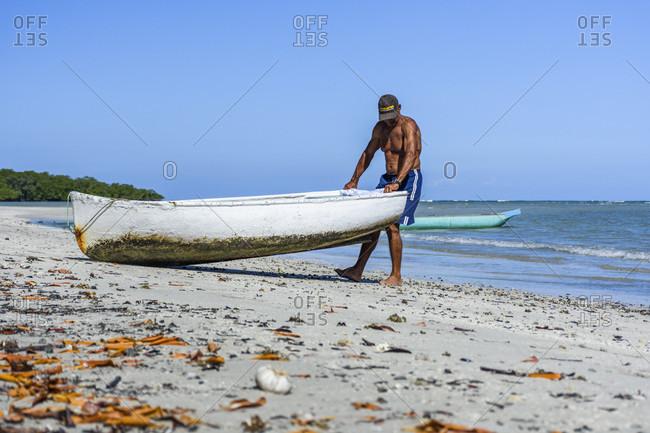 Morro de Sao Paulo, Bahia, Brazil - February 16, 2018: Man dragging boat to sea, Morro de Sao Paulo, Bahia, Brazil