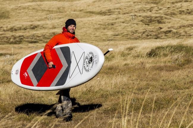Petit Saint bernard, Savoie, France - February 16, 2018: Stand up paddle boarder standing in meadow, Little St Bernard Pass, Savoie, France