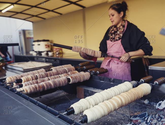 Prague, Prague, czech republic - October 5, 2015: Woman baking rolled pastry, Prague, Czech Republic