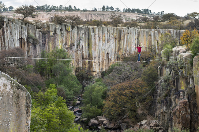 Aculco, Estado de Mexico, Mexico - November 13, 2012: Person balancing on rope hanging across canyon cliffs, Aculco, State of Mexico, Mexico