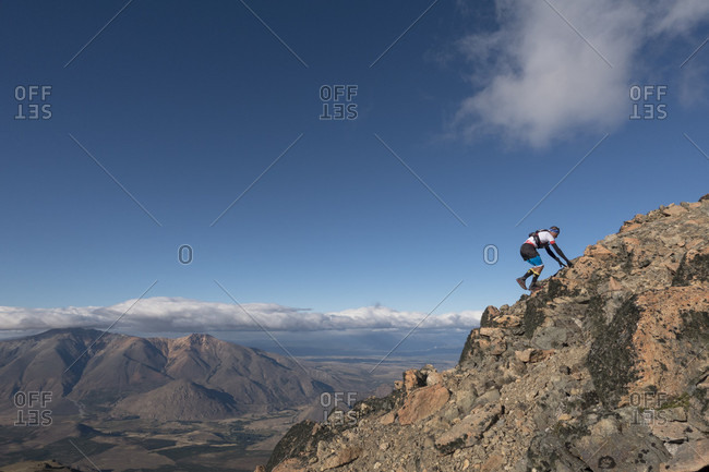 Esquel, Chubut, Argentina - March 5, 2017: Man climbing rocky mountain against clouds and sky, Esquel, Chubut, Argentina