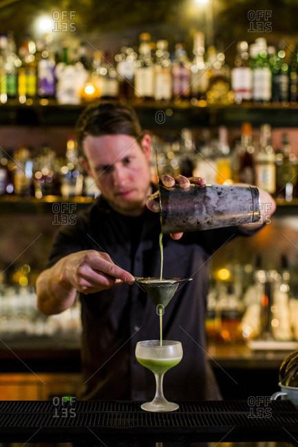 Seattle, Washington, USA - February 4, 2017: Bartender making cocktail at bar, Capital Hill, Seattle, Washington State, USA