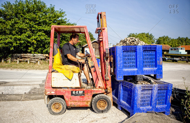 Arcachon, Gironde, France - June 24, 2017: Man stacking oyster crates at oyster farm using forklift, La Teste-de-Buch, Gironde, France