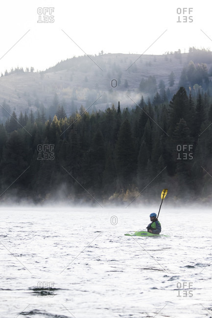 Jackson Hole, WY, USA - September 20, 2016: Person kayaking on Snake River against forested hills during foggy weather, Jackson Hole, Wyoming, USA